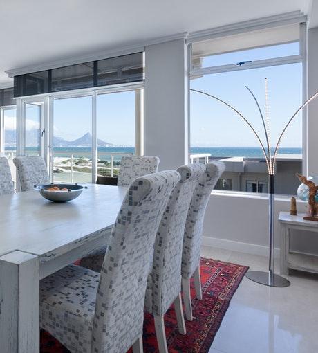 foto de uma sala de jantar com cortina rolo na janela